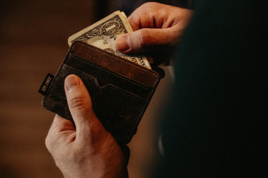 pessoa a pegar em carteira com dinheiro