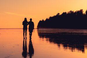 homem e mulher a caminhar numa praia